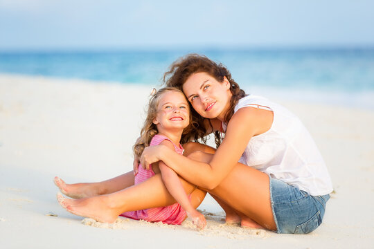 Mother with little daughter resting on ocean beach, Maldives. Family on the beach concept.