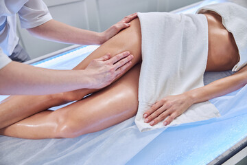 Fototapeta Professional masseur doing lymphatic drainage for young woman in cabinet obraz