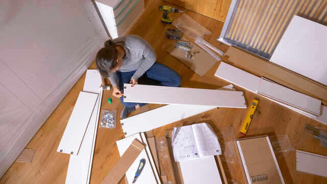 TOP DOWN Woman glues and hammers pegs into plywood board while assembling closet