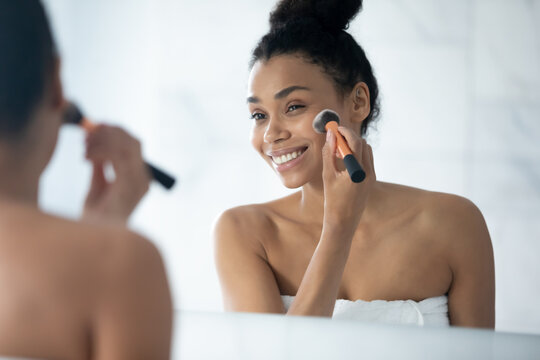Happy African American beautiful girl putting makeup on smooth facial skin at mirror, smiling at reflection, using cosmetic big brush with powder for applying foundation on face. Beauty care concept