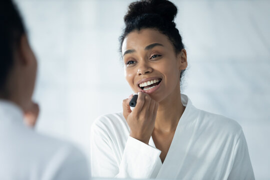 Happy beautiful millennial Black girl putting on lipstick, rouging lips, looking in mirror, smiling. Young woman in white bathrobe applying makeup after morning shower. Glamour, female routine concept