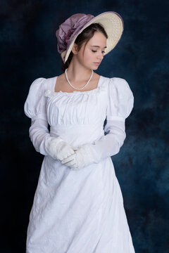 A young Regency woman wearing a white muslin dress and a straw bonnet