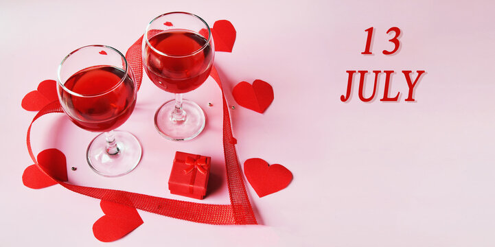 calendar date on light background with two glasses of red wine, red gift box and red hearts with copy space. July 13 is the thirteenth day of the month