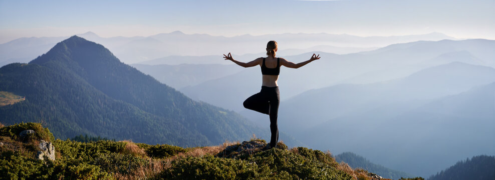 Back view of woman practicing yoga in evening mountains. Meditating female is balancing on one leg after sunset outdoor. Concept of harmony with nature.