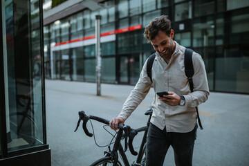 Obraz Happy cyclist in the city using phone - fototapety do salonu