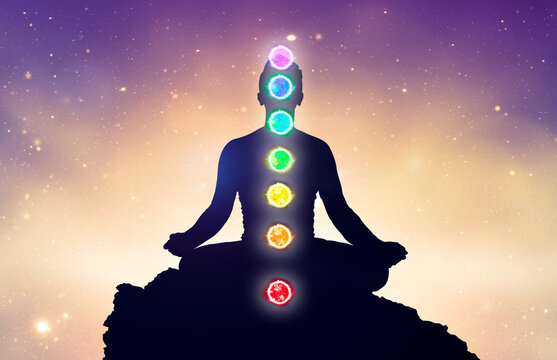 Chakras and meditating men in yoga lotus position. Mindfulness and self awereness practice. Silhiuette of meditation with chakras on stars background.