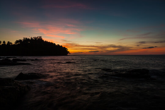 Vivid sunset sky waterscape and silhouette forest island