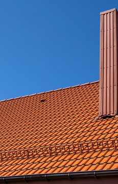 Red corrugated metal profile roof installed on a modern house. The roof of corrugated sheet. Roofing of metal profile wavy shape. Modern roof made of metal. Metal roofing.