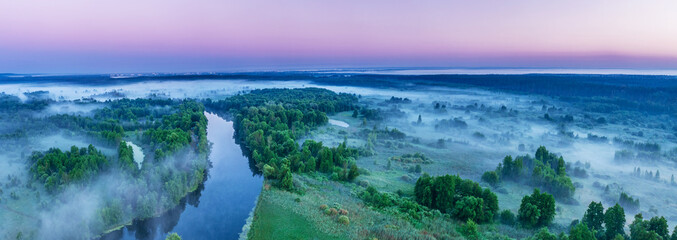 Smoky morning mist over the river. Beautiful panoramic view of river and green banks of the river in the early summer morning. - fototapety na wymiar