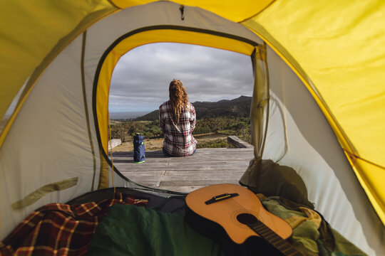Rear view of caucasian woman camping, sitting outside tent on mountainside deck admiring view