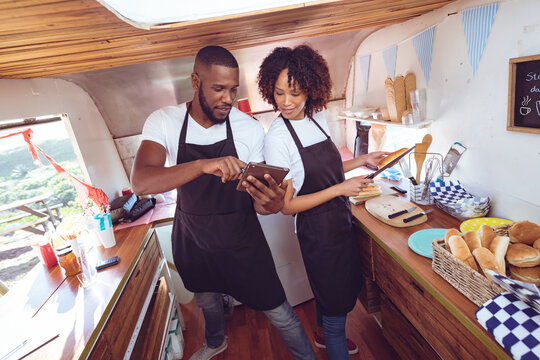 Diverse couple behind counter using tablet in food truck