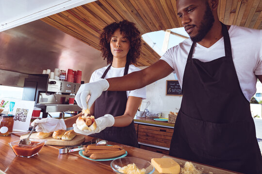 Diverse couple preparing hot dogs behind counter in food truck