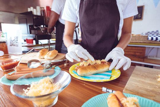 Mixed race woman garnishing hot dog behind counter in food truck