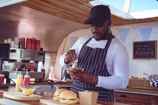 African american man in food truck preparing order with hamburgers on worktop