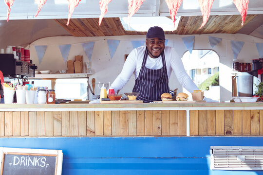 Portrait of smiling african american man in food truck with hamburgers on worktop