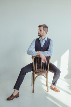 Portrait of a man in a shirt and waistcoat sitting and leaning on the back of a chair in sunlight