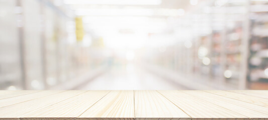 Fototapeta Wood table top with supermarket grocery store blurred background with bokeh light for product display obraz