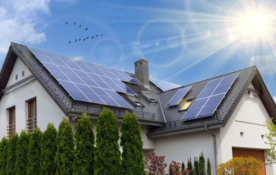 Beautiful modern house with solar panels. Clear sky, sun.