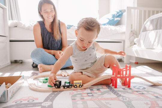 Mother and toddler boy playing with car wooden railway on floor at home. Early age education development. Kids building rail road and playing educational toy trains cars. Leisure activity for kids