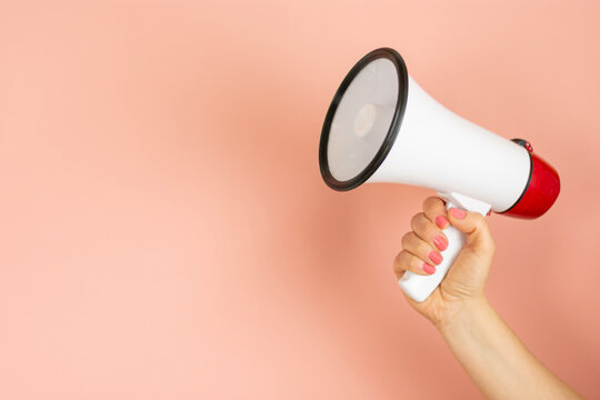 Woman holding megaphone on pink background