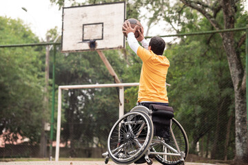 person in wheelchair throwing basketball in open court..