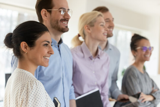 Close up happy diverse motivated employees team standing in office, smiling successful confident workers coworkers or interns looking to aside, positive excited business people staff department