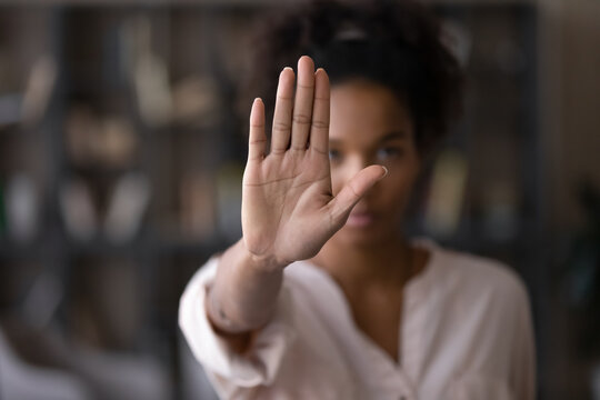 Close up focus on female mixed race palm hand showing stop sign, serious african american woman protesting against bullying in society, sexual or racial discrimination, denying family abuse indoors.