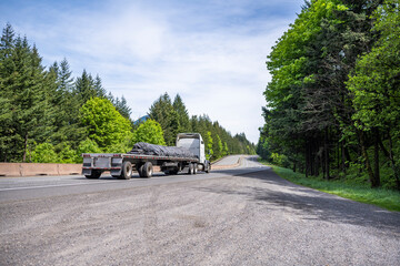 Fototapeta White industrial grade big rig semi truck transporting covered cargo on flat bed semi trailer running on the curving road in Columbia Gorge obraz