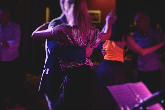Couples dancing traditional latin argentinian dance milonga in the ballroom, tango salsa bachata kizomba lesson in the red, purple and violet lights, dance festival