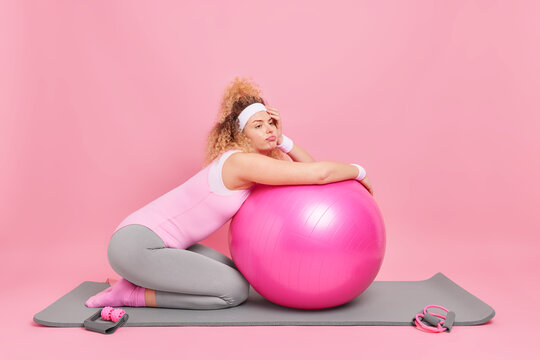 Displeased bored woman leans at fitness ball rests after exercise session dressed in activewear takes break from workout poses on karemat isolated over pink background. Health care pilates practice