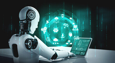 Obraz Robot humanoid use laptop and sit at table for global network connection using AI thinking brain , artificial intelligence and machine learning process for 4th industrial revolution . 3D illustration. - fototapety do salonu