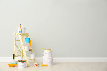 Obraz Decorator's kit of tools and paints near light wall indoors. Space for text - fototapety do salonu