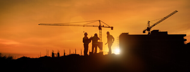 Fototapeta Silhouette engineer construction work control and tower crane background on natural sunset sky.,Heavy industry and building construction work concept in banner obraz