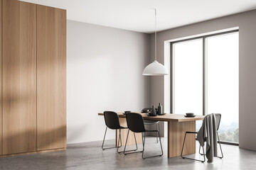 Obraz Stylish wood and concrete interior of dining room with design table and four black chairs. Minimalist style of home decor. Panoramic window with view. Empty copy space wall. - fototapety do salonu