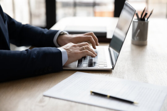 Hands of businessman using app laptop at workplace, typing on keyboard. Business professional working at computer in office, chatting online, browsing internet, writing article or report. Close up