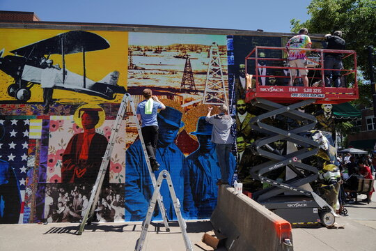 Workers put up a mural of historic photos of Black Wall Street ahead of the 100 year anniversary of the 1921 Tulsa Massacre in Tulsa