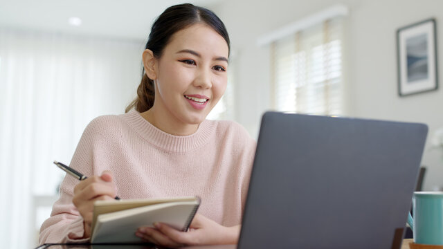 Young attractive business asian woman talking about sale report in video call conference on notebook computer online meeting in working from home, Working remotely and Social isolation concept.