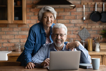 Happy older clients online e-services users concept. Mature spouses smile look at camera while spend time together in domestic kitchen with laptop, buy on internet, making easy delivery order remotely - fototapety na wymiar