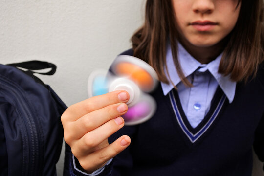 Schoolgirl playing with pop it  fidget spinner toy in school