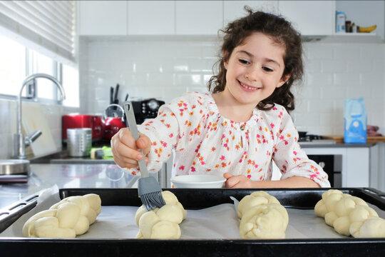 Happy Jewish girl baking sweet Challah bread for Sabbath Jewish Holiday