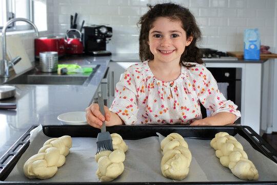 Cute Jewish girl baking sweet Challah bread for Sabbath Jewish Holiday