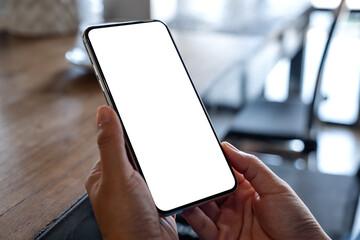 Fototapeta Mockup image of a woman holding mobile phone with blank white desktop screen obraz