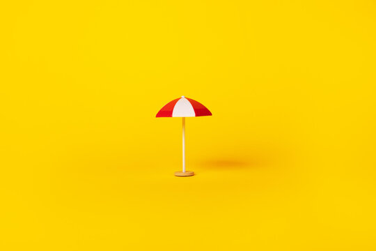 red and white beach umbrella over yellow background, summertime and vacation concept