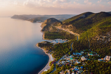 Aerial view of coastline with blue sea, mountains with trees, cliffs with sunset light and clouds. - fototapety na wymiar