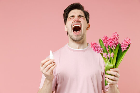 Sick unhealthy ill allergic man has red eyes runny stuffy sore nose suffer from allergy symptoms hay fever hold blooming flower plant uses nasal drops isolated on pastel pink color background studio.