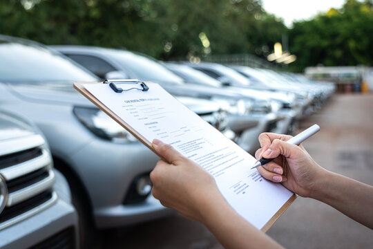 Action of a customer is signing on the agreement term of car rental service. Close-up and selective focus a human's hand with blurred background of cars in row. Business and transportation concept.
