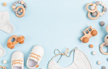 Fototapeta Baby shoes, bib and teether on pastel background. Organic newborn accessories obraz