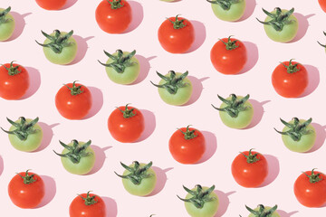 A pattern of green and red tomatoes with a stalk on a pink background. Minimal vegetablest flat lay