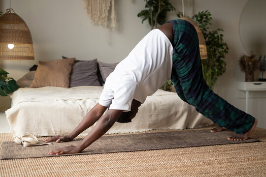 Young african man working out, standing in yoga downward facing dog pose, adho mukha svanasana