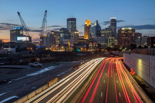 Image of Minneapolis skyline and highway with traffic lines leading to the city.